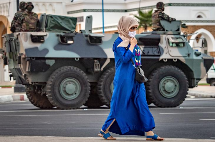 A woman walks past a tank and soldiers on a street in Tangier, Morocco, on 11 August 2020  (photo: FADEL SENNA/AFP)