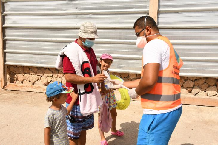 A health worker distributes a mask to a man on a beach in Rabat, Morocco, on 27 August 2020 (photo: imago images/Xinhua | Chadi via www.imago-images.de)