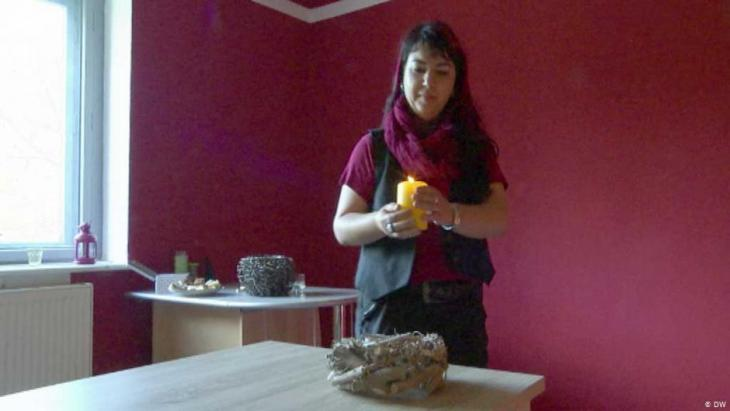 Staff member with candle in a hospice (photo: DW)
