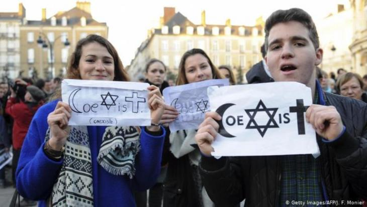 People hold signs reading 'co-exist' at a rally in Rennes (photo: Getty Images/ AFP/ J.Monier)