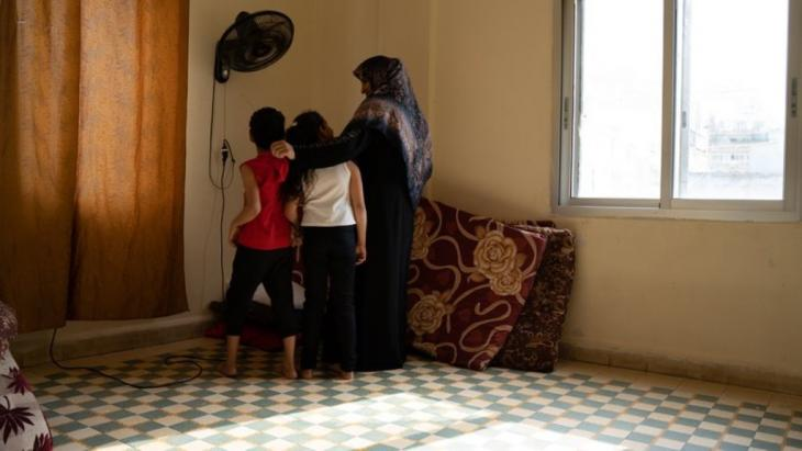 Salha Khalaf Mohamed with two of her children in their bedroom. The explosion destroyed the bed frame, now they sleep on mattresses on the floor (photo: Andrea Backhaus)