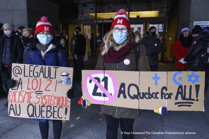 "Demonstrators stand outside the courthouse on the first day of the constitutional challenge to Bill 21, which bans public workers in positions of ""authority"" from wearing religious symbols, before the Quebec Superior Court in Montreal on 2 November 2020 (photo: THE CANADIAN PRESS/Paul Chiasson)"