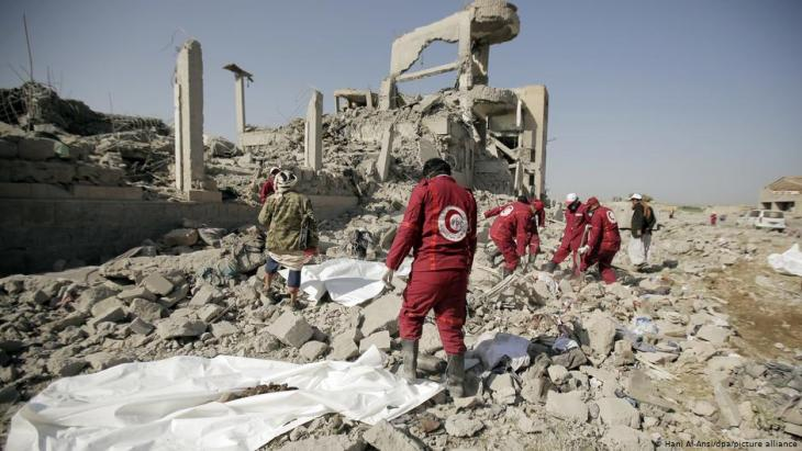 Aid workers recover dead bodies from the rubble of a prison in Yemen after an air strike by the Saudi military coalition (photo: Hani Al-Ansi/dpa/picture-alliance)