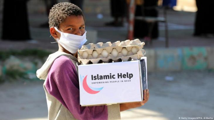 Yemen | Child with face mask carries relief supplies in Taez (photo: Getty Images/AFP/A.Al-Basha)
