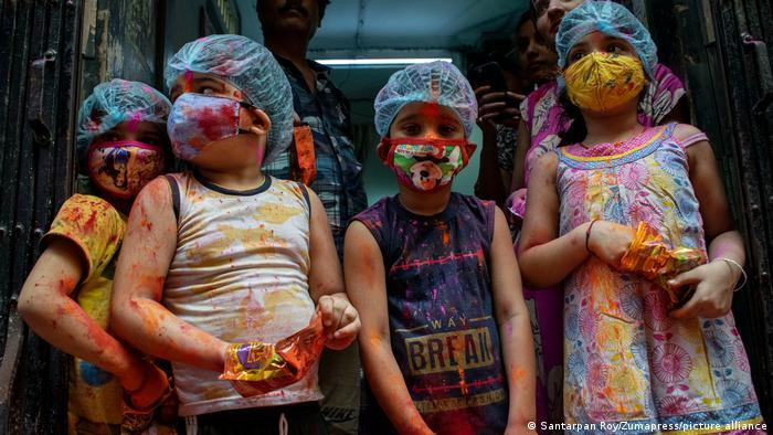 Children in masks and caps hold bags of coloured powder (photo: Santarpan Roy/Zumapress/picture-alliance)