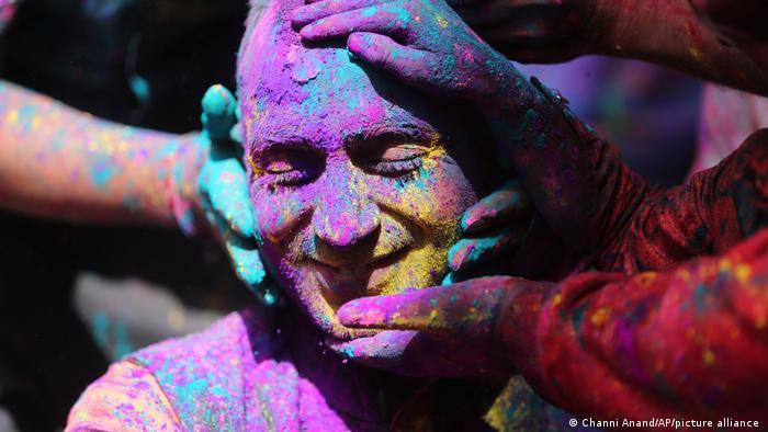 People touch the face of a man covered in coloured powder (photo: Channi Anand/AP/picture-alliance)