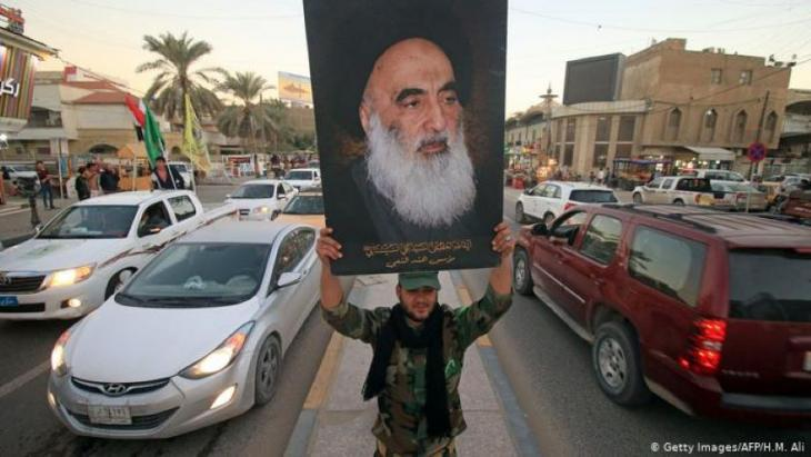 A member of the Hashed al-Shaabi, or Popular Moblization Units, carries a picture of Sistani during victory celebrations in December 2017 after Iraq declared Islamic State defeated (photo: Getty Images/AFP/H. M. Ali)