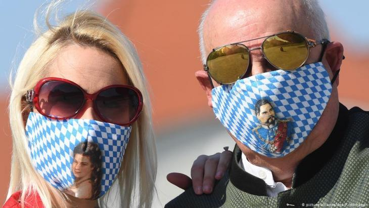 A man and a woman wear face masks with traditional Bavarian patterns (photo: picture-alliance/dpa/F. Hornager)