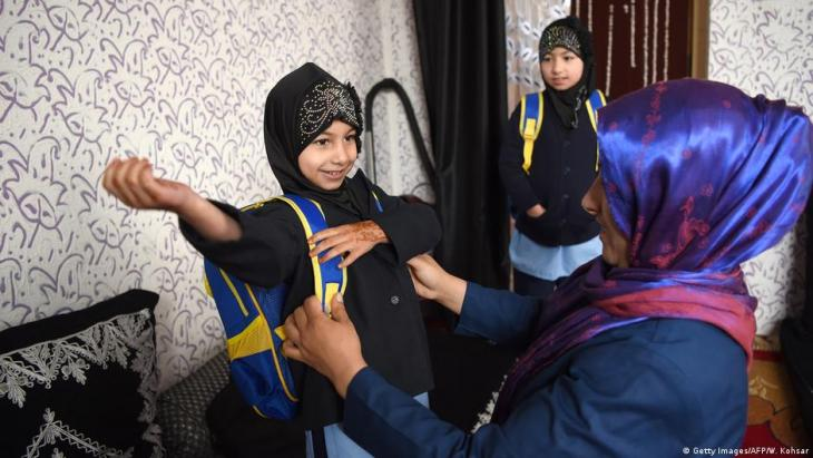 Afghan sisters getting ready to leave for school in Kabul (photo: Getty Images/AFP/W. Kohsar)