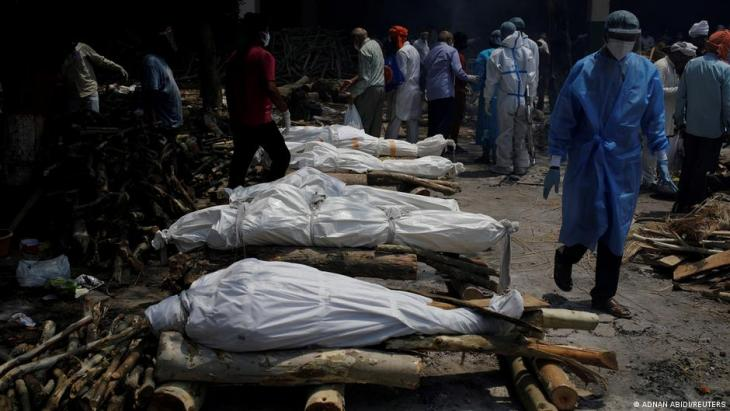 A health worker wearing personal protective equipment (PPE) walks past the funeral pyres of those who died from the coronavirus disease (COVID-19) during a mass cremation at a crematorium in New Delhi, India, 26 April 2021 (photo: REUTERS/Adnan Abidi)