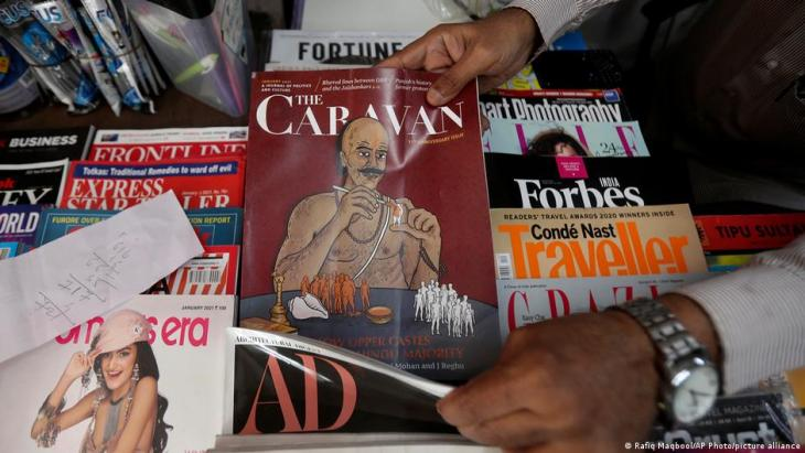 A vendor reaches out for a copy of The Caravan, India's leading investigative magazine, in Mumbai, India, 5 February 2021 (photo: AP Photo/Rafiq Maqbool)