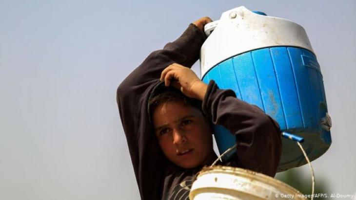 A Syrian boy carries water in a container (photo: Getty Images/AFP/S. Al-Doumy)