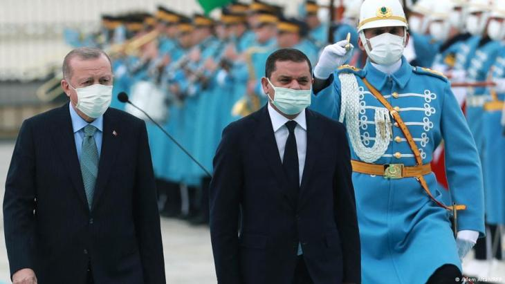 Turkish President Recep Tayyip Erdogan (L) and Libyan government of national unity prime minister Abdul Hamid Dbeibah (R) walk past honour guards during the official ceremony prior to their meeting in Ankara on 12 April 2021 (photo by Adem ALTAN / AFP)