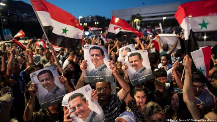 Cheering people with a portrait of head of state Assad (photo: Hassan Ammar/AP Photo/picture-alliance)