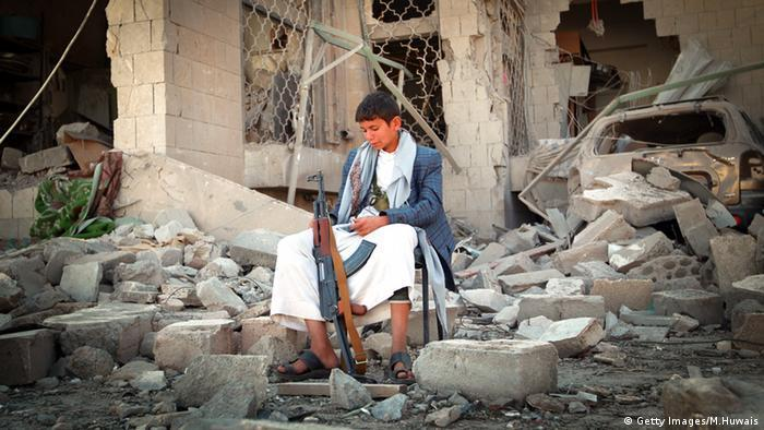 A child Houthi soldier sits among the rubble of a house in the Yemeni capital, Sanaa (photo: Getty Images/M. Huwais)