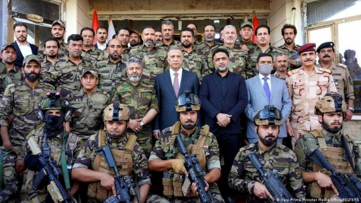 Iraqi Prime Minister Mustafa al-Kadhimi poses for a group photo with Shia fighters from Saraya al-Salam, who are loyal to cleric Muqtada al-Sadr, in Samara, Iraq, 16 June 2021 (photo: Iraqi Prime Minister Media Office/Reuters)