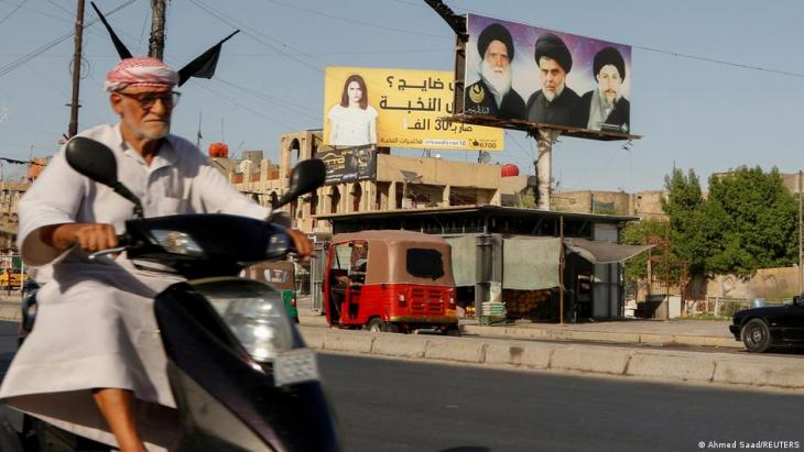 A man drives his motorbike near a poster of the late Grand Ayatollah Mohammed Sadiq al-Sadr, his son Iraqi Shia cleric Muqtada al-Sadr, and Iraq's late Shia cleric Mohammed Baqir al-Sadr, in the Sadr City district of Baghdad, Iraq, 21 June 2021 (photo: Ahmed Saad/Reuters)