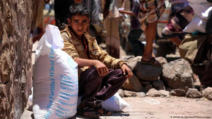 Yemeni boy sits with a sack of wheat flour, an essential aid handout in war-torn Yemen (photo: Ahmad Al-Basha/AFP/Getty Images)