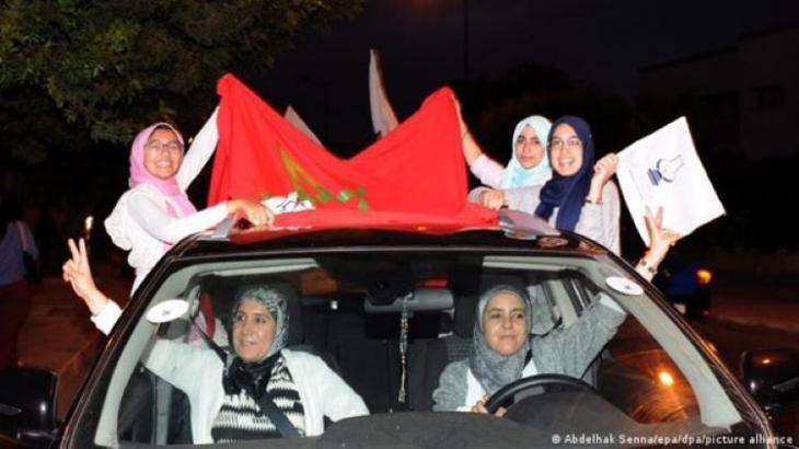 Supporters of Morocco's PJD (Justice and Development Party) in a car with flags (photo: Abdelhak Sennalepa/dpa/picture-alliance)