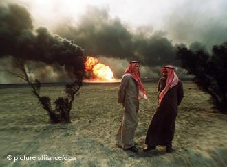 Two Kuwaiti men standing in the desert, in the background burning oil fields, set on fire by Iraqi troops (photo: picture-alliance/dpa)