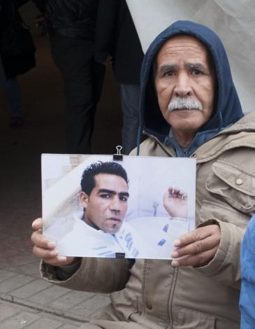 Mohamed holds up a photo of his son during a demonstration by relatives of the victims of the revolution (photo: Sarah Mersch)