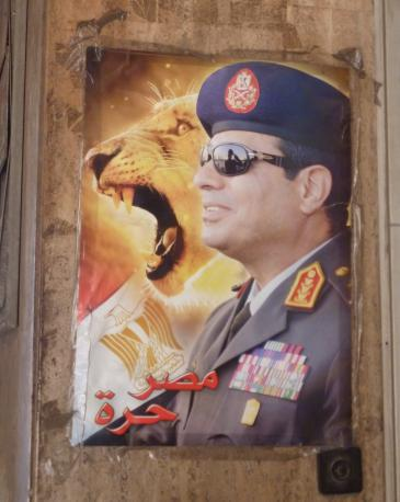 A poster depicting Abdul Fattah al-Sisi beside the Egyptian flag and the head of a lion (photo: Arian Fariborz)