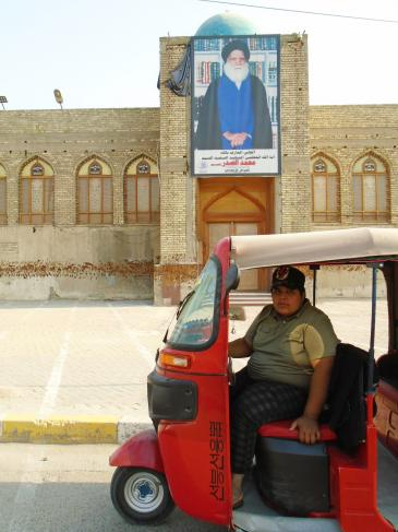 Hussein in his bright red tuk-tuk in Sadr City (photo: Birgit Svensson)