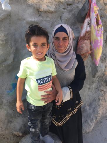 Three-year-old Muhammad Bakr Hussein with his mother Bara'a Hamandi in front of the family's home in the West Bank village of Mufkara (photo: Inge Gunther)
