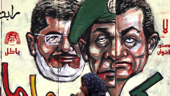 Three faces symbolizing the reinstatement of former powers in Egypt: President Morsi behind images of Mubarak and Tantawi (photo: Reuters)
