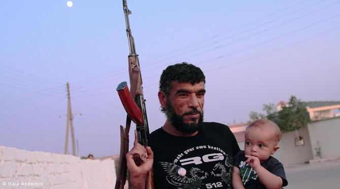 Libyan opposition fighter with child: As the conflict continues, fighters are provided with everything they need by their families
