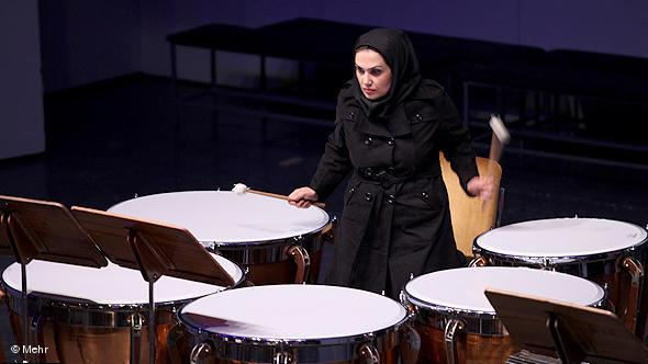 A young woman playing the tympani in an orchestra