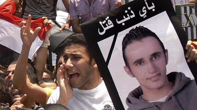 Egyptian demonstrators on Tahrir Square with a placard bearing the image of Khaled Said, the young man beaten to death by police