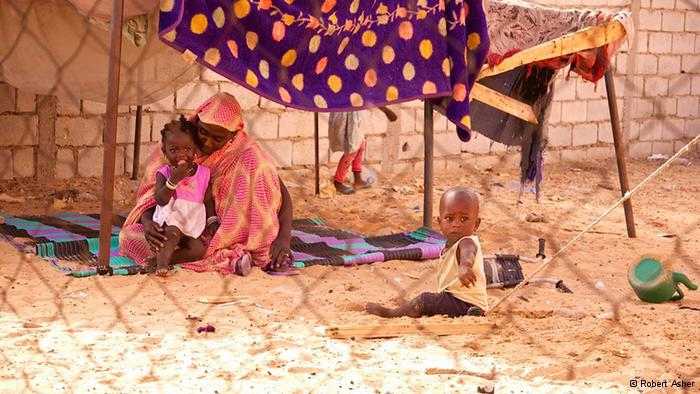 Matallah, a former slave, in her makeshift home, with two of her young children (photo: Robert Asher)