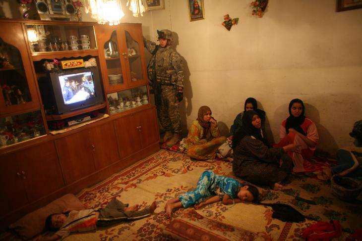 US soldiers search a home in a late-night raid as children lie asleep (photo: Michael Kamber)