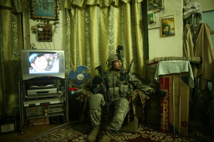 A US soldier sits in an armchair during a search of a private home (photo: Michael Kamber)