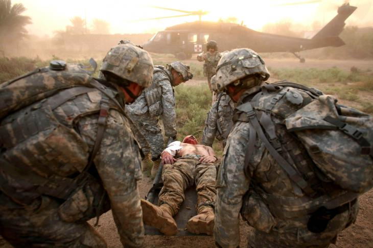 A wounded US soldier is carried to a helicopter (photo: Michael Kamber)