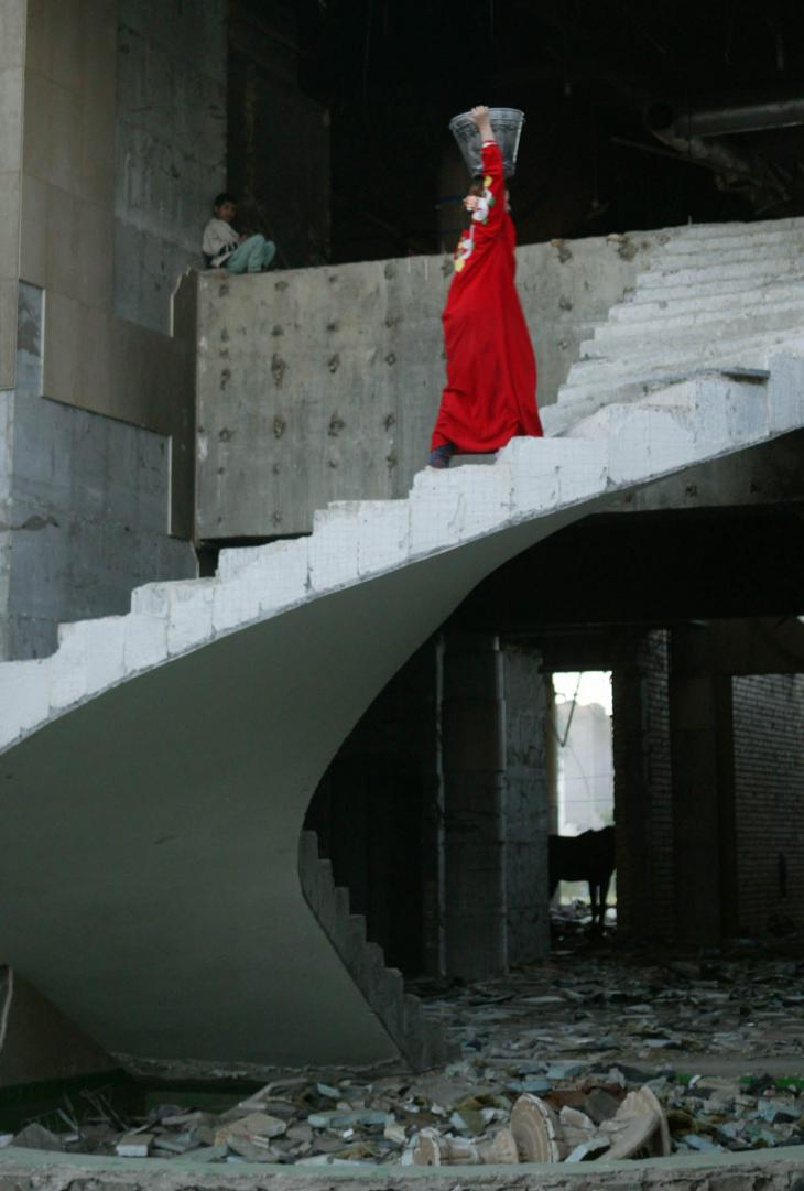 A woman walks up the stairs of the ruined Baghdad Iraqi Air Force Club while a child looks on (photo: Michael Kamber)