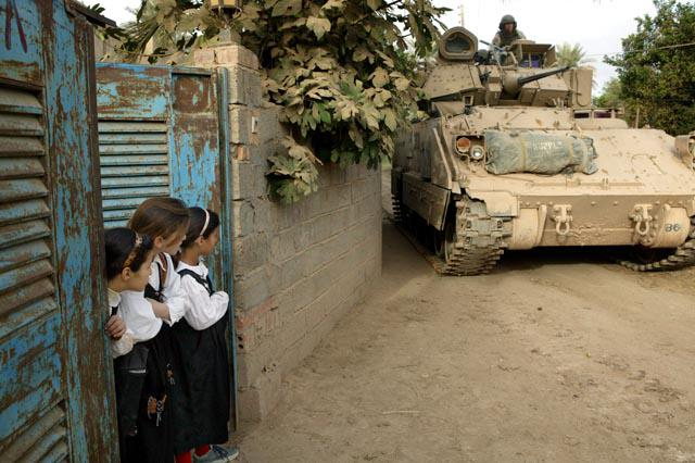 Schoolgirls watch US soldiers driving by in a tank (photo: Michael Kamber)
