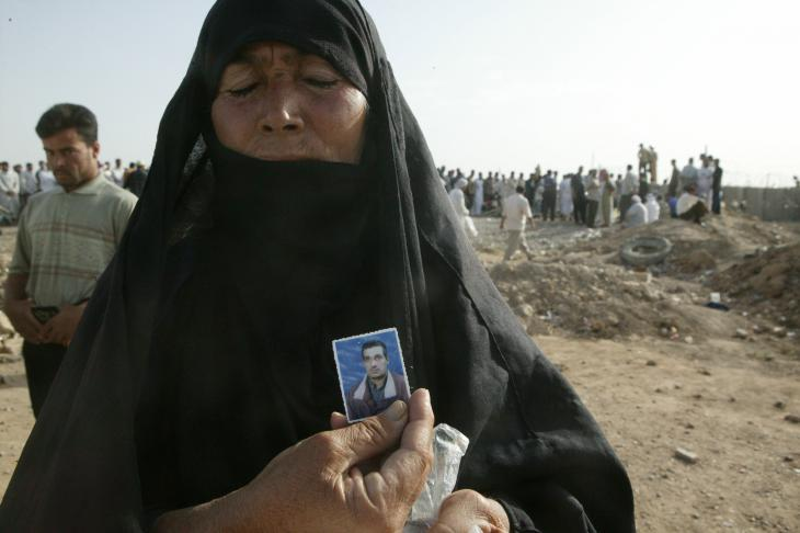 A woman holds up a photo of her son outside Abu Ghraib (photo: Michael Kamber)