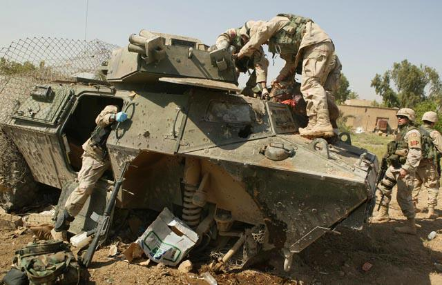 US soldiers pull the driver from an armoured vehicle destroyed by an IED (photo: Michael Kamber)