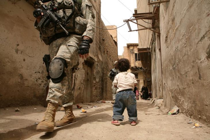 A small child watches US soldiers patrolling the streets of Khadamiya (photo: Michael Kamber)