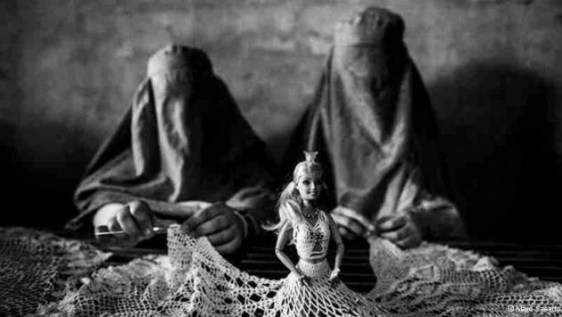 Women dressed in burqas making lace for a dress worn by a Barbie doll (photo: Majid Saeedi)