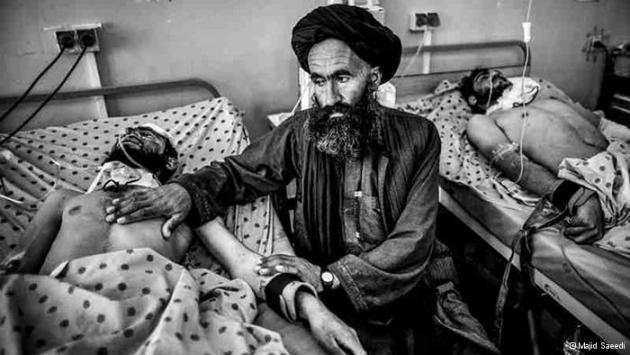 A man touches the chest and arm of another man lying injured in a hospital bed (photo: Majid Saeedi)