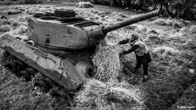 A farmer piles bundles onto a Soviet tank in his field (photo: Majid Saeedi)