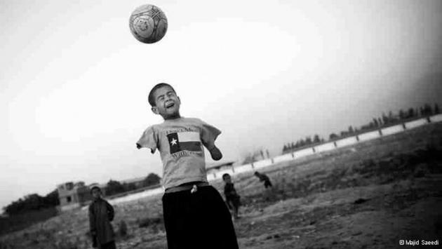 A boy with no arms jumps up to head a football (photo: Majid Saeedi)