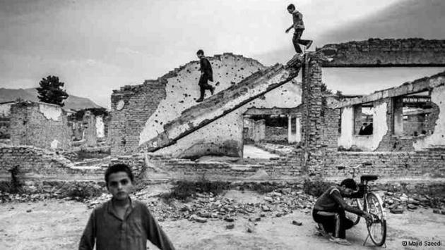 Children on and in front of ruined buildings (photo: Majid Saeedi)