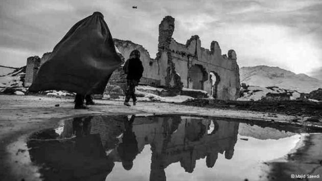 An Afghan woman and child walk past a ruined house (photo: Majid Saeedi)
