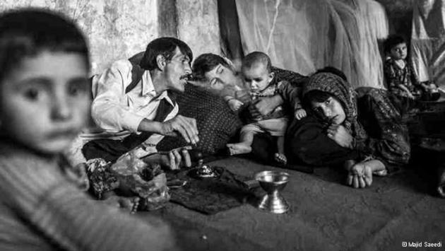 A man smokes opium in the presence of women and children, exhaling smoke into an infant's face (photo: Majid Saeedi)