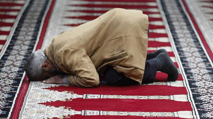 Man praying on a red carpet in Amman airport. Photo: picture alliance/Robert Harding World Imagery