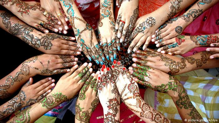 A circle of 17 hands painted with henna in different colours. Photo: picture alliance/dpa